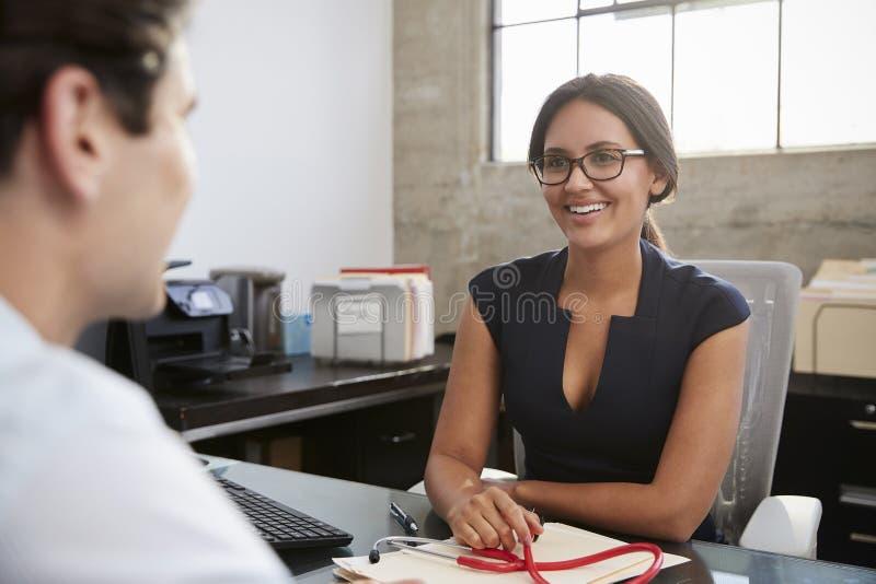Ung kvinnlig doktor i regeringsställning som möter den manliga patienten arkivfoton