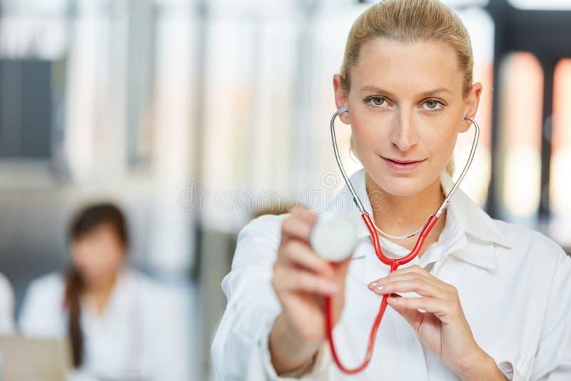Ung kvinnlig doktor med stetoskopet i sjukhuset royaltyfri foto