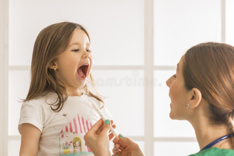 Ung kvinnlig doktor som ger liten flickamedicin royaltyfri bild
