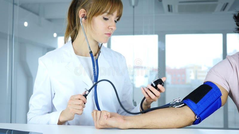 Ung kvinnlig doktor som kontrollerar blodtryck av patienten i klinik arkivfoton