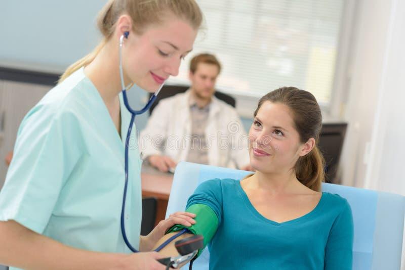 Ung kvinnlig doktor som kontrollerar blodtryckpatienten royaltyfri fotografi