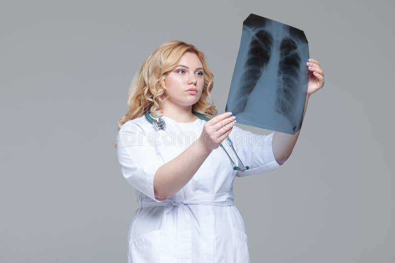 Ung kvinnlig doktor som ser r?ntgenstr?lebilden av lungor royaltyfri fotografi