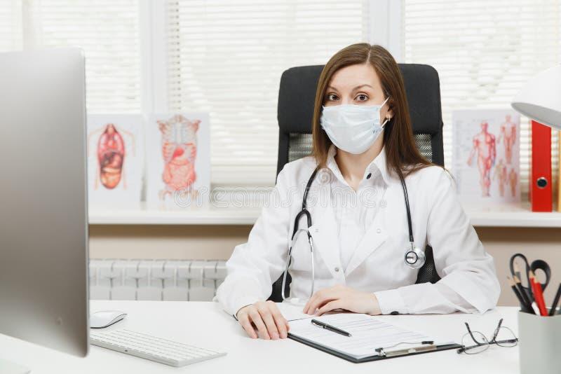 Ung kvinnlig doktor som sitter på skrivbordet som arbetar på den moderna datoren med medicinska dokument i ljust kontor i sjukhus royaltyfria bilder