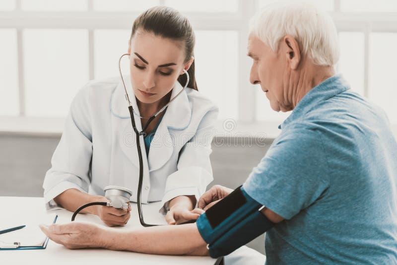 Ung kvinnlig doktor som undersöker den höga patienten arkivbilder
