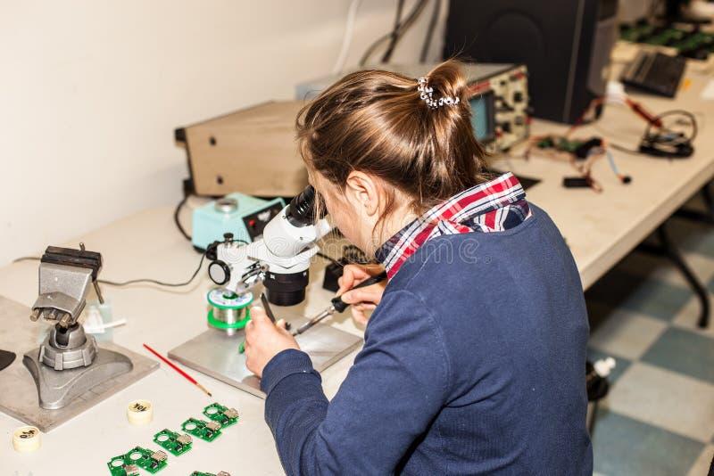 Ung kvinnlig elektronisk tekniker på arbete royaltyfria foton