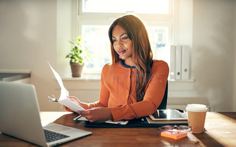 Ung kvinnlig entreprenör som arbetar i hennes inrikesdepartementet som läser välling royaltyfri bild