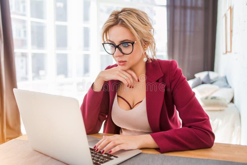 Ung kvinnlig entreprenör som sitter på tabellen i hennes inrikesdepartementet som arbetar på bärbara datorn royaltyfri foto