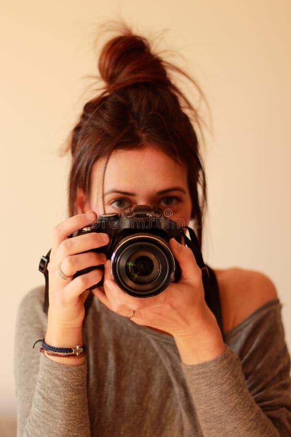 Ung kvinnlig fotograf med kameran på mjuk bakgrund arkivbild