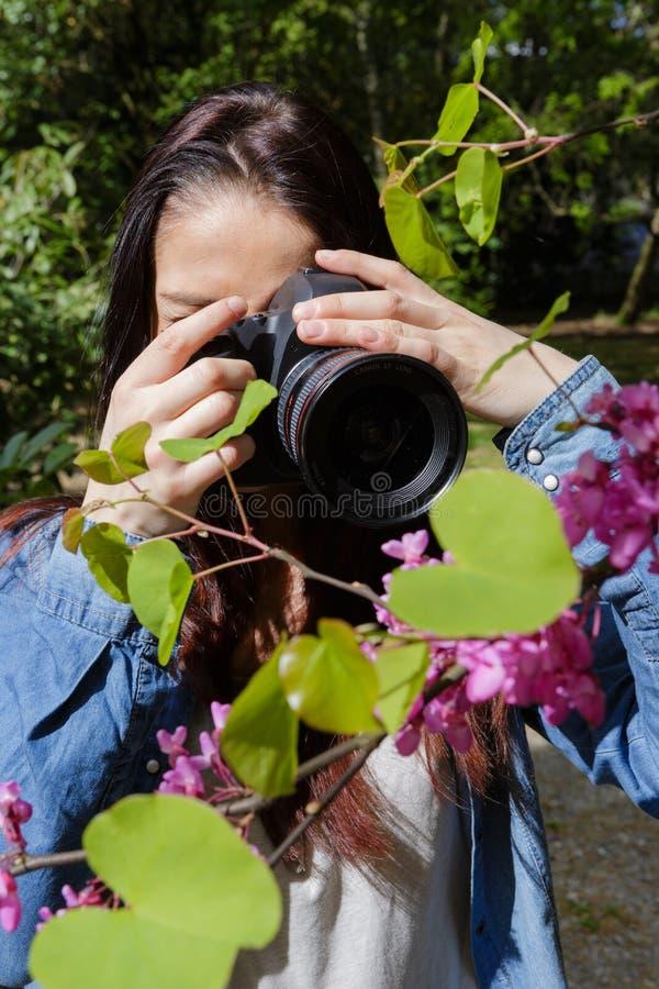 Ung kvinnlig fotograf som utomhus använder kameran arkivfoto