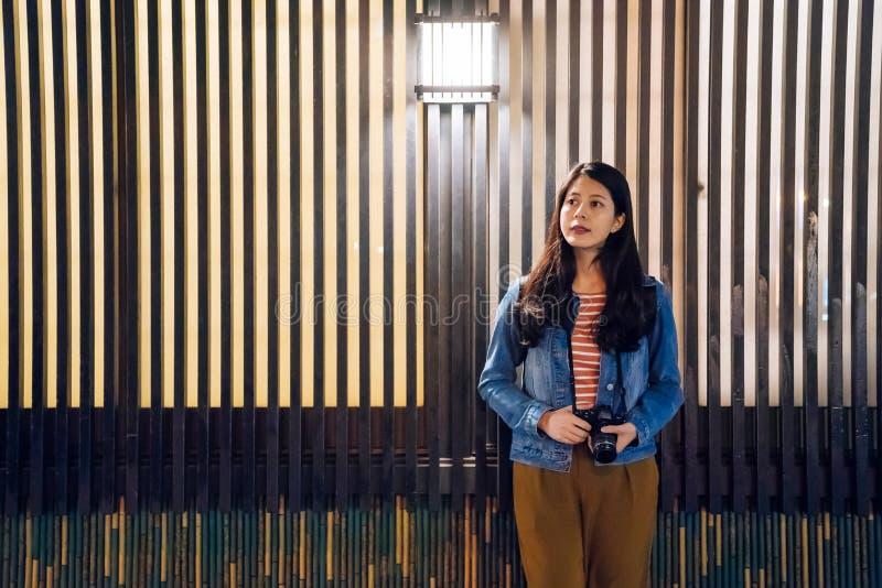 Ung kvinnlig fotografinnehavkamera som därefter stading träväggen utanför den väntande på matställen för restaurang härlig kvinna royaltyfria bilder