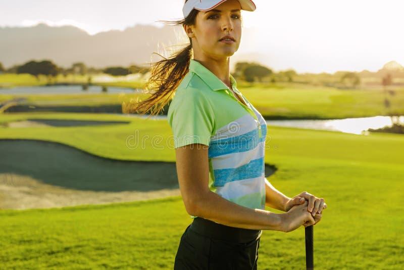 Ung kvinnlig golfare med golfklubben fotografering för bildbyråer