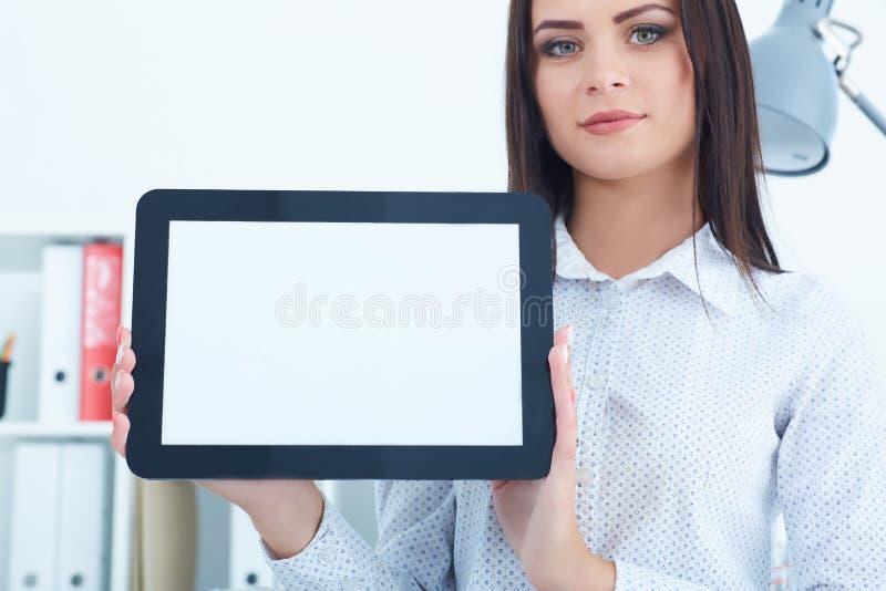 Ung kvinnlig hållande minnestavla för affärskvinna med den tomma skärmen i händer som sitter på kontoret royaltyfri fotografi
