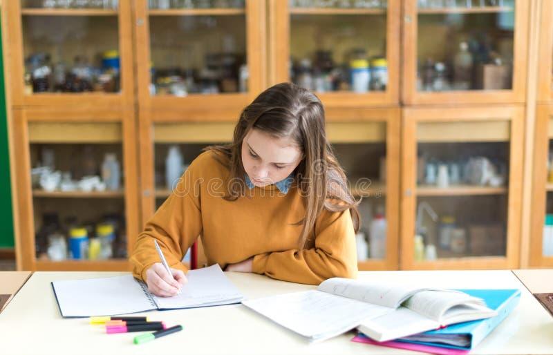 Ung kvinnlig högskolestudent i kemigrupp som skriver anmärkningar Fokuserad student i klassrum royaltyfri fotografi