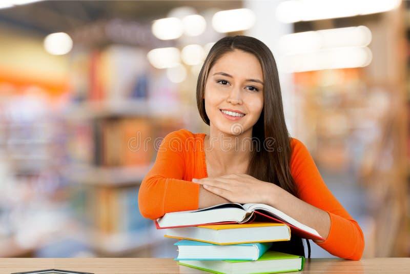 Ung kvinnlig högskolestudent och buntbok på royaltyfri bild