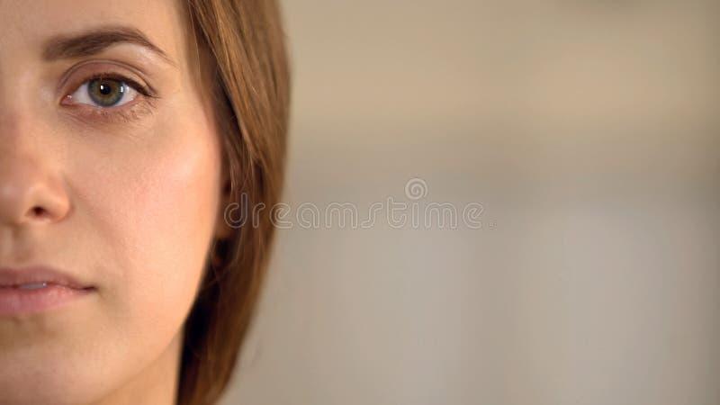 Ung kvinnlig halv framsida som ser in i kameran, genomsnittlig kvinnaåsiktstatistik arkivfoton