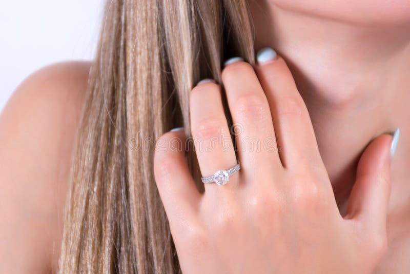 Ung kvinnlig hand med kopplingsvigselringen på finger- och handinnehav i hår royaltyfri bild