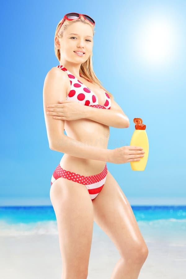 Ung kvinnlig i bikinin som sätter på solkräm, yttersida på en strand royaltyfri foto