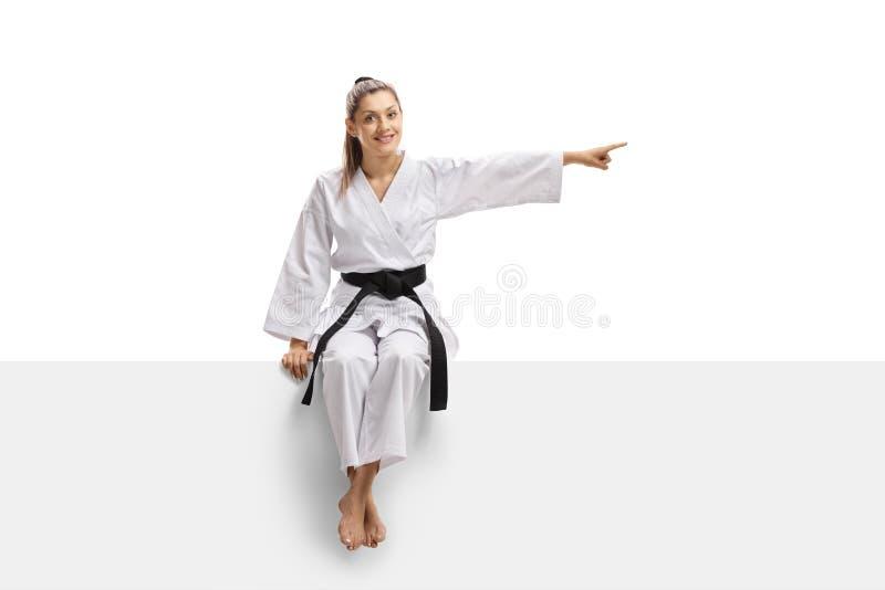 Ung kvinnlig i kimonot och det svarta bältet som sitter på en panel och pekar till sidan arkivfoto