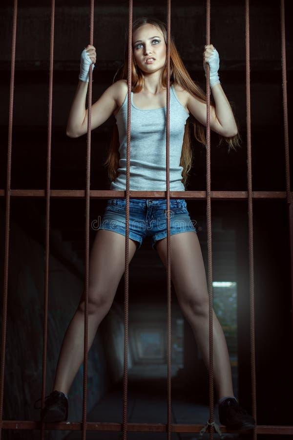 Ung kvinnlig kämpe på ett metallstaket arkivbilder