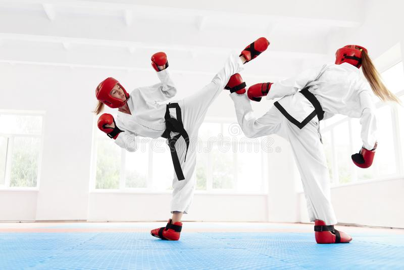 Ung kvinnlig kämpeboxning genom att använda karateteknik arkivbild