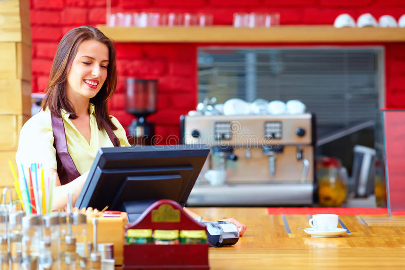 Ung kvinnlig kassörska som fungerar på kassan i kafé arkivbilder