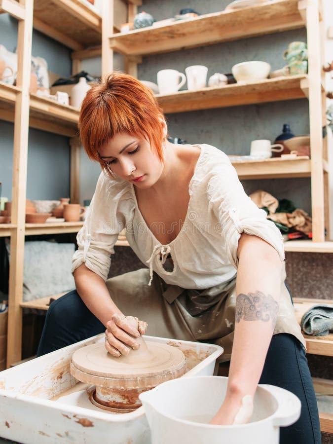 Ung kvinnlig keramiker som arbetar på studion royaltyfri bild