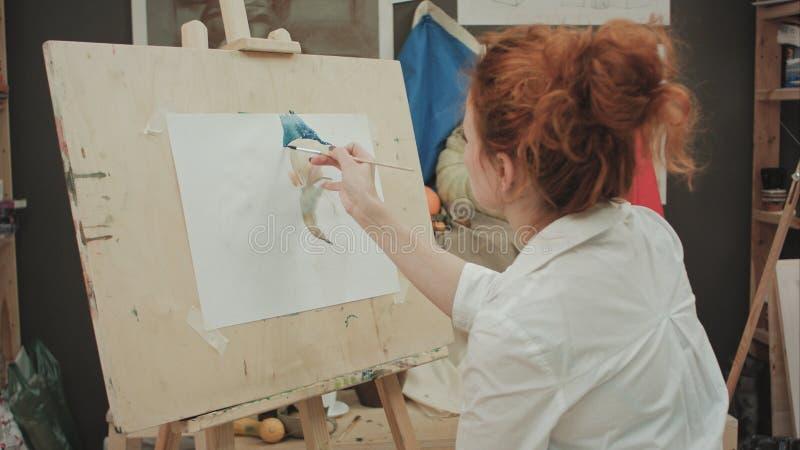 Ung kvinnlig konstnärmålningstilleben i studio arkivbilder
