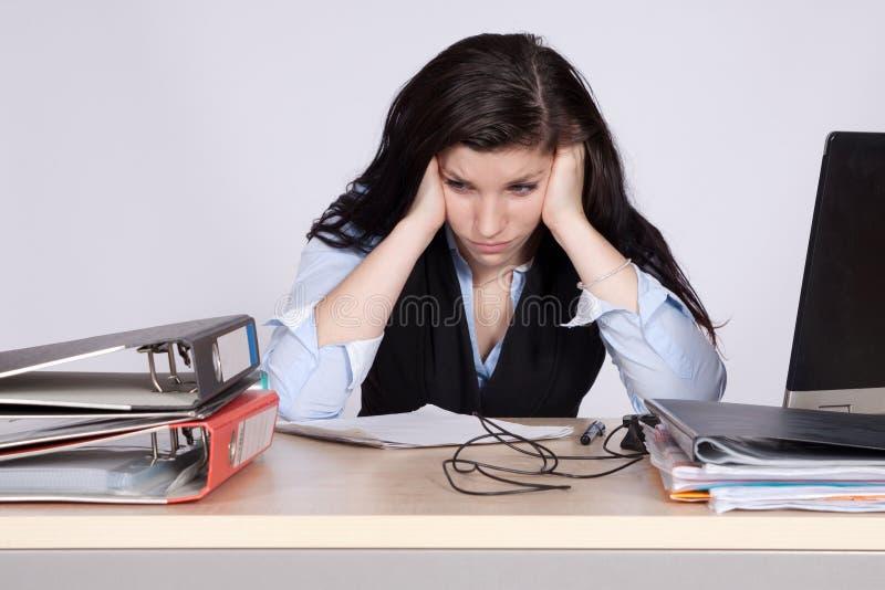 Ung kvinnlig kontorsarbetare på skrivbordet arkivbild