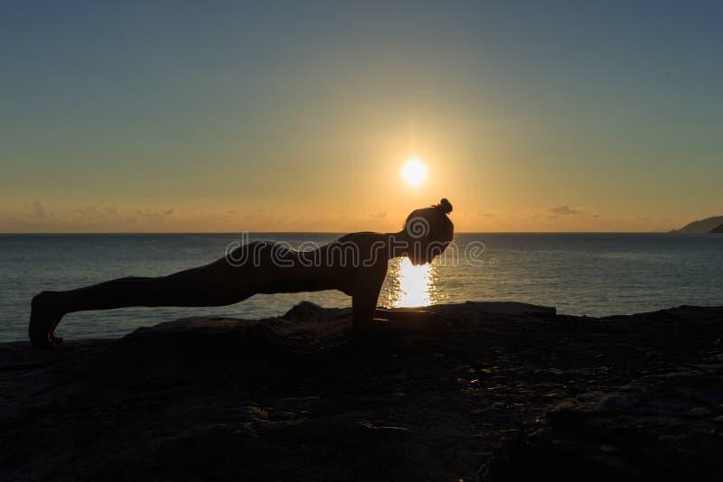 Ung kvinnlig kontur som gör plankaövning på en strand på soluppgång royaltyfri foto