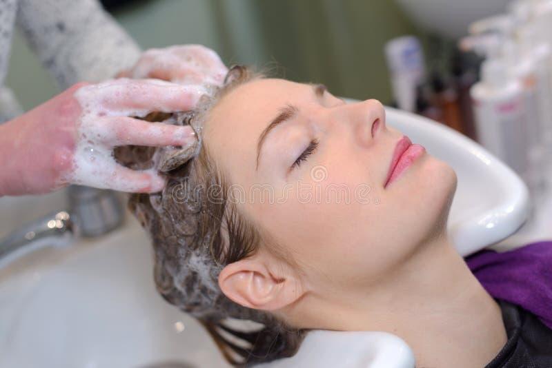 Ung kvinnlig kvinna som har den influtna skönhetsalongen för hår fotografering för bildbyråer