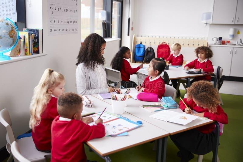 Ung kvinnlig lärare för begynnande skola som sitter på en tabell i ett klassrum med hennes elever arkivbilder