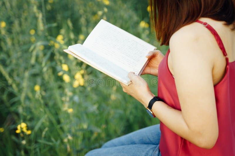 Ung kvinnlig läsebok som är utomhus- på semester arkivfoton