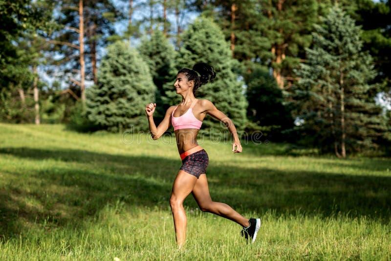 Ung kvinnlig l?pare som joggar under utomhus- genomk?rare i en parkera H?rlig passformflicka isolerad kvinna f?r white f?r vikt f royaltyfri bild
