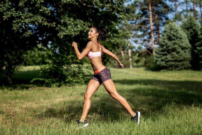 Ung kvinnlig l?pare som joggar under utomhus- genomk?rare i en parkera H?rlig passformflicka isolerad kvinna f?r white f?r vikt f royaltyfria bilder