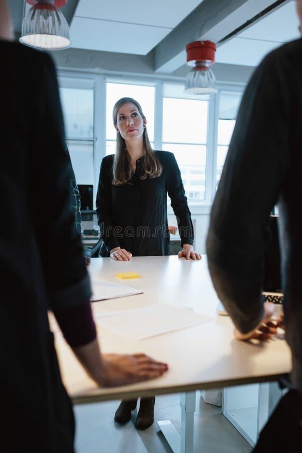 Ung kvinnlig ledare med kollegor runt om en tabell arkivfoton