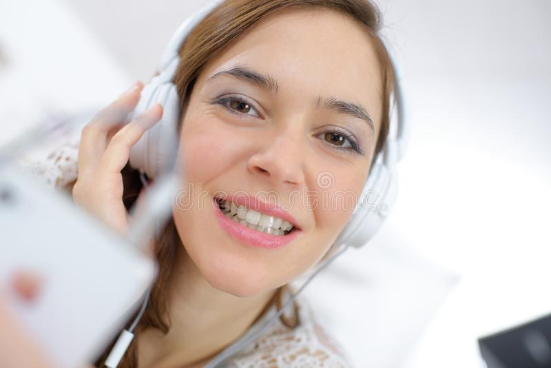 Ung kvinnlig med hörlurar arkivfoto