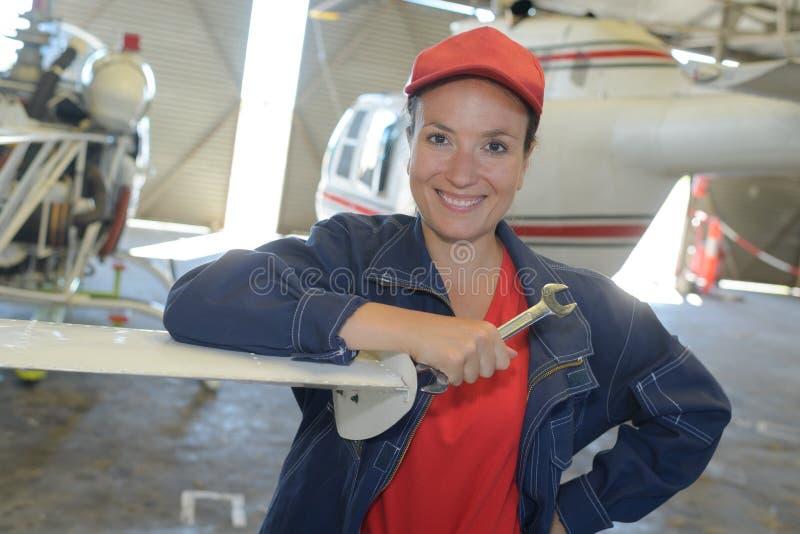 Ung kvinnlig med jetflygplan för skiftnyckelfixandedel arkivfoto