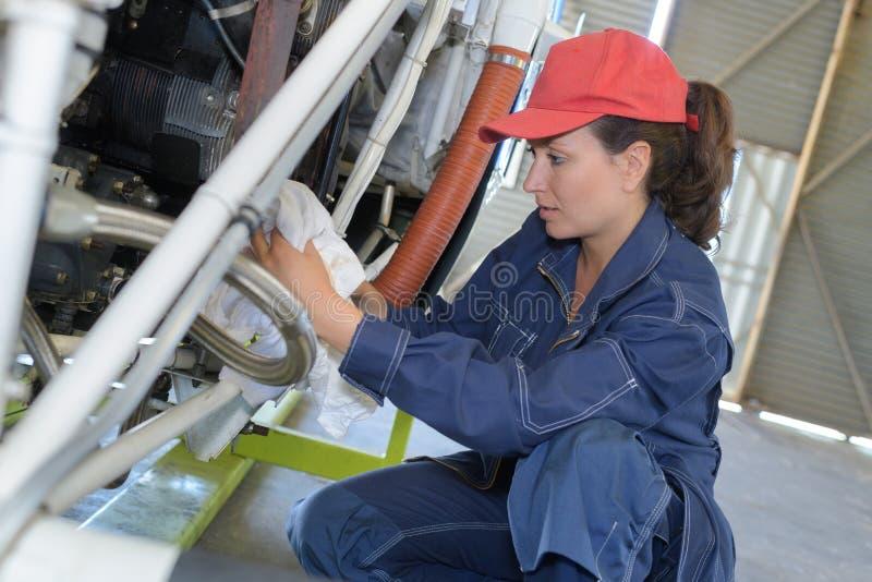 Ung kvinnlig med jetflygplan för skiftnyckelfixandedel arkivbild