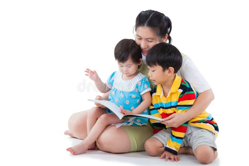 Ung kvinnlig med två lilla asiatiska barn som läser en bok royaltyfri fotografi