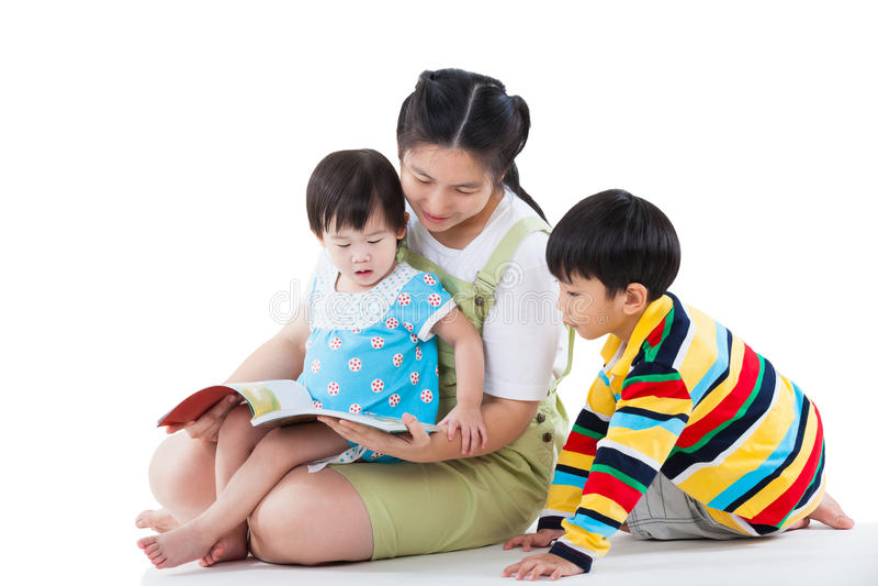 Ung kvinnlig med två lilla asiatiska barn som läser en bok arkivfoton