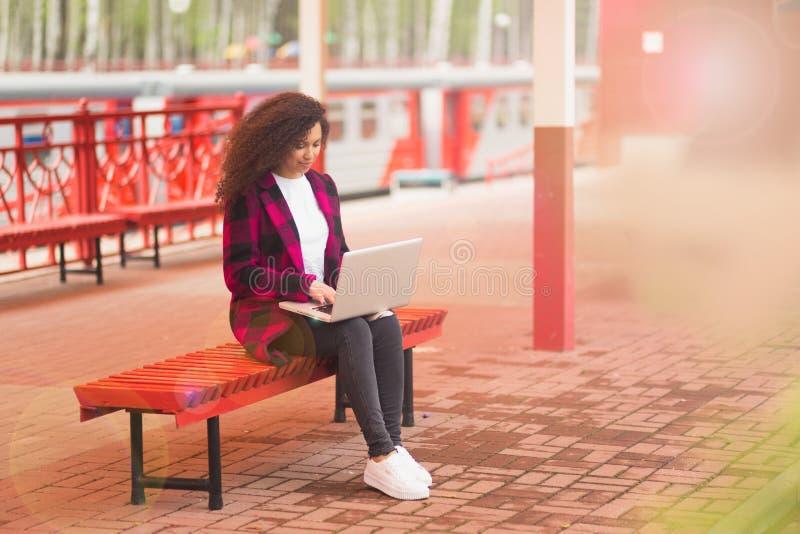 Ung kvinnlig passagerare för flygplats på smart telefon- och bärbar datorsammanträde i slutlig korridor, medan vänta på hennes fl arkivfoton