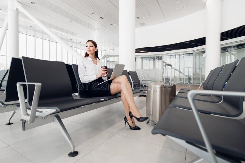 Ung kvinnlig passagerare f?r flygplats p? smart telefon- och b?rbar datorsammantr?de i slutlig korridor, medan v?nta p? hennes fl arkivbild