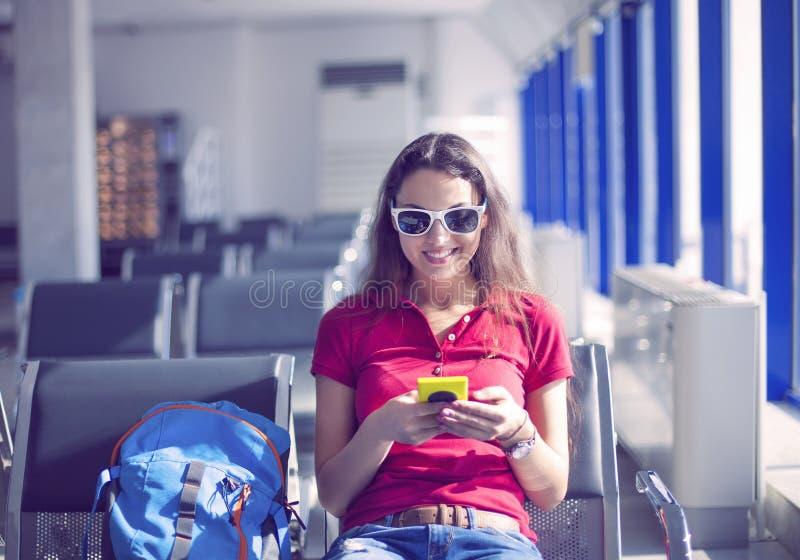 Ung kvinnlig passagerare på den smarta telefonen på porten som väntar i termina royaltyfri bild