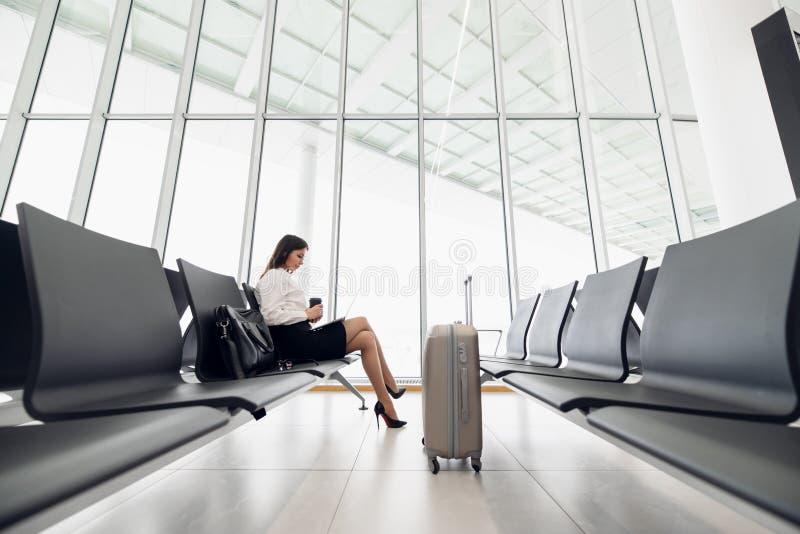 Ung kvinnlig passagerare p? flygplatsen, genom att anv?nda hennes minnestavladator, medan v?nta p? hennes flyg arkivfoto