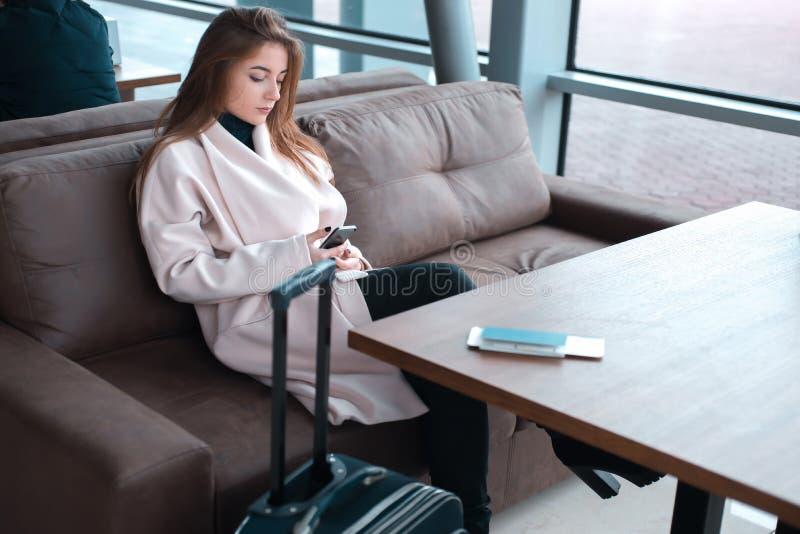 Ung kvinnlig passagerare som använder telefonen på flygplatsen arkivfoto