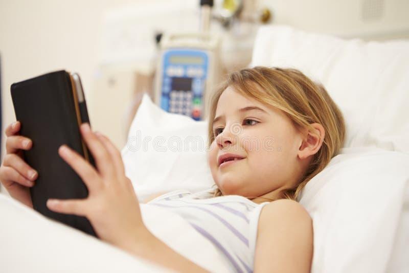 Ung kvinnlig patient som använder den Digital minnestavlan i sjukhussäng royaltyfria foton