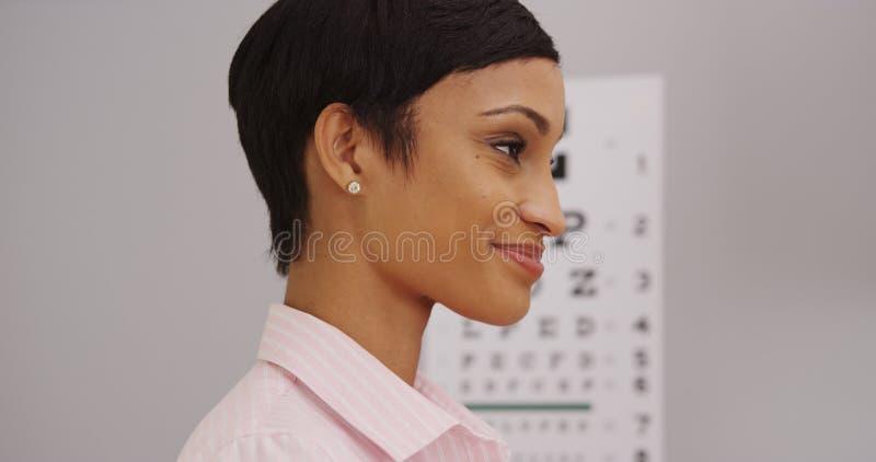 Ung kvinnlig patient som får en ögonexamen arkivbild