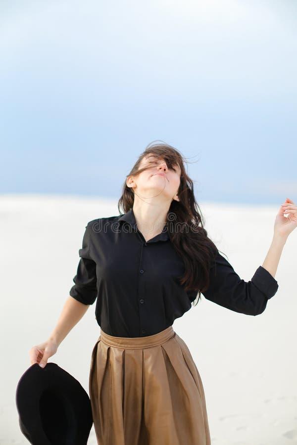 Ung kvinnlig person som bär den svarta blusen och brunt kjolanseende i vit bakgrund och håller hatten royaltyfri foto