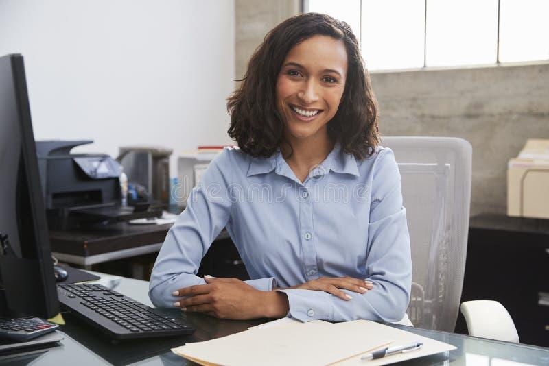 Ung kvinnlig professionell på skrivbordet som ler till kameran fotografering för bildbyråer