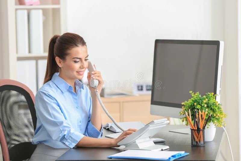 Ung kvinnlig receptionist som talar på telefonen arkivfoton